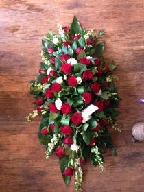 Red, white and green casket spray.